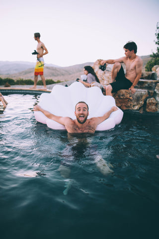 Kololo Pink Seashell floaty guy holding onto floaty in the pool smiling