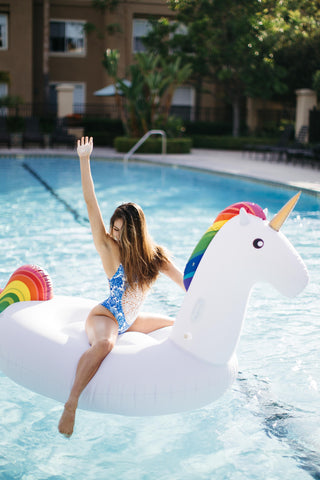Kololo Giant Unicorn floaty girl blue swimsuit one hand up looking sideways
