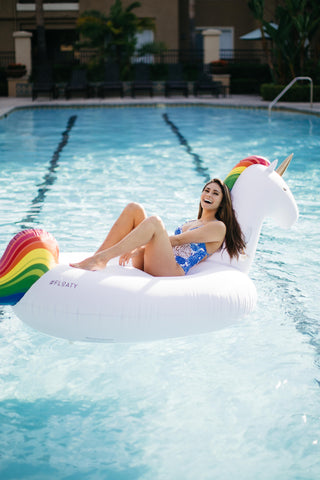 Kololo Giant Unicorn floaty girl laying on the floaty smiling