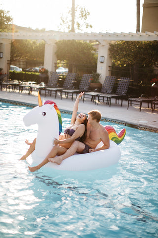 Kololo Giant Unicorn rainbow floaty girl and guy sitting and laughing