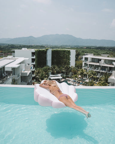 Kololo Pink Seashell floaty girl lounging at an infinity pool with a mountain view