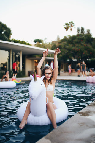 Kololo Big Unicorn rainbow floaty girl wearing glasses at a pool party smiling with arms raised