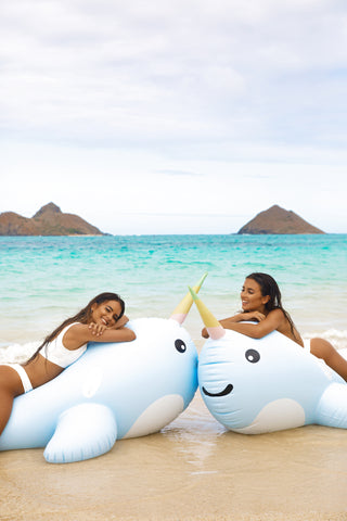 Kololo Giant Narwhal floaty 2 girls at the beach up close smiling lounging