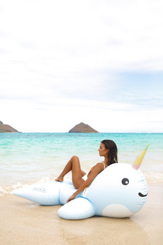 Kololo Giant Narwhal floaty girl at the beach lounging and leaning on narwhal looking away