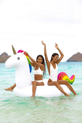 Kololo Giant Unicorn rainbow floaty 2 girls sitting enjoying at the beach