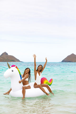 Kololo Giant Unicorn rainbow floaty 2 girls sitting enjoying at the beach smiling hands up