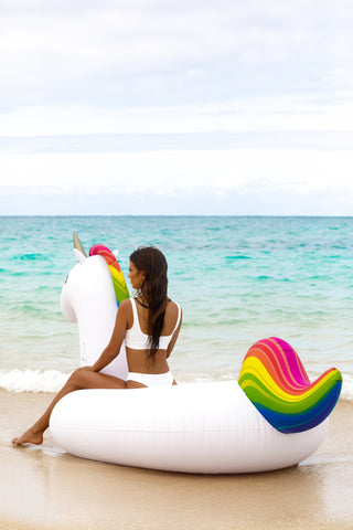 Kololo Giant Unicorn rainbow floaty girl sitting looking at the ocean