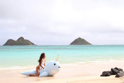 Kololo Giant Narwhal floaty girl sitting on floaty by the shore looking away
