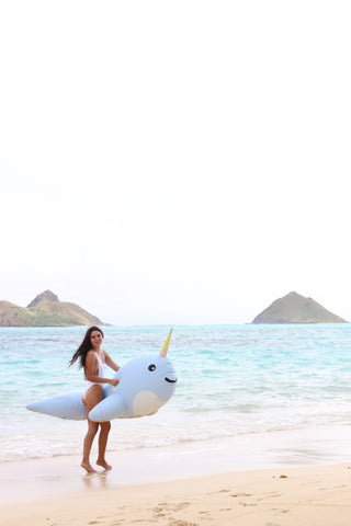 Kololo Giant Narwhal floaty girl looking at the camera smiling holding floaty at the beach