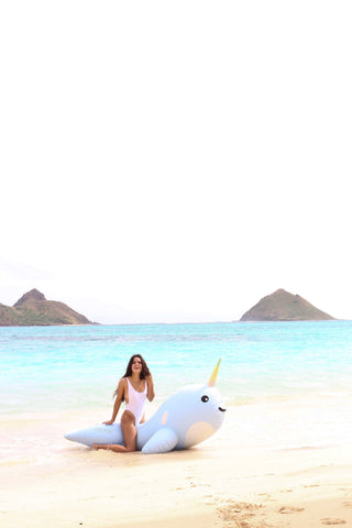 Kololo Giant Narwhal floaty at the beach girl kneeling smiling touching hair