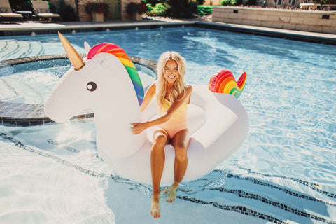 Kololo Big Unicorn rainbow floaty girl sitting on unicorn holding onto it