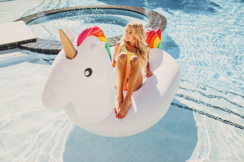Kololo Giant Unicorn rainbow floaty girl lounging looking away