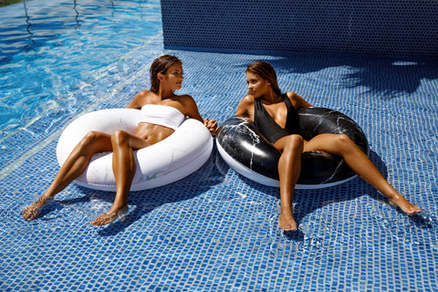 Kololo Black Marble Tube Pink Marble Tube floaty 2 girls relaxing at the pool