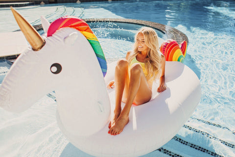 Kololo Giant Unicorn rainbow floaty girl lounging looking away smiling widely