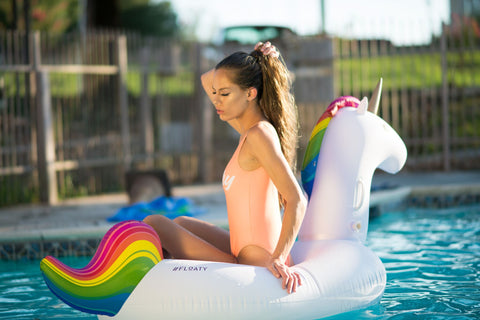 Kololo Big Unicorn rainbow floaty girl sitting on unicorn fixing hair