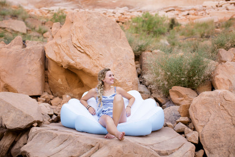 Kololo Blue Seashell floaty girl lounging smiling rocky area