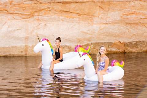 Kololo Giant Unicorn Big Unicorn rainbow floaty two girls sitting smiling