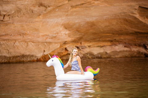 Kololo Big Unicorn rainbow floaty girl at a lake sitting and smiling