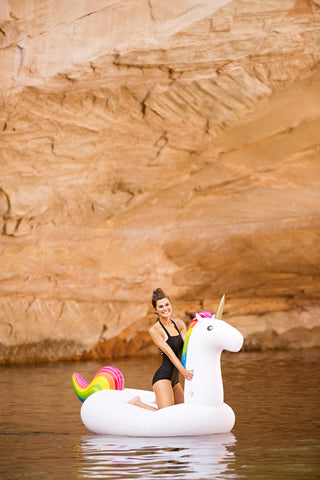 Kololo Giant Unicorn rainbow floaty girl at a lake kneeling smiling