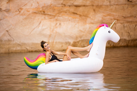 Kololo Giant Unicorn rainbow girl at a lake lounging smiling