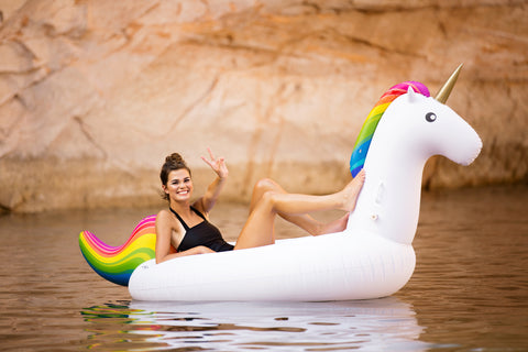 Kololo Giant Unicorn rain bow floaty girl at a lake smiling peace sign