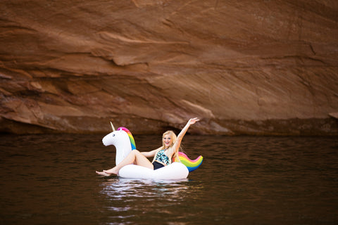 Kololo Big Unicorn rainbow floaty girl smiling arm outstretched sitting down