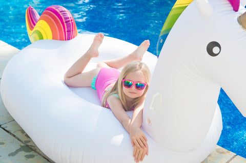 Kololo Big Unicorn rainbow floaty little girl with sunglasses lounging
