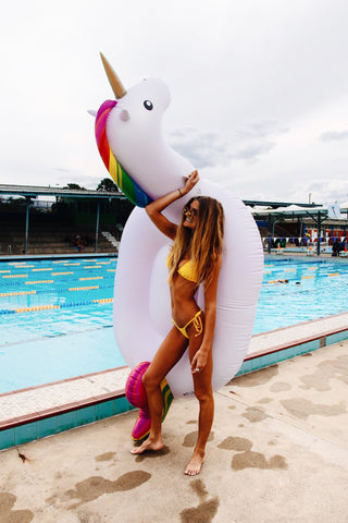 Kololo Giant Unicorn rainbow floaty girl standing by the pool holding the unicorn