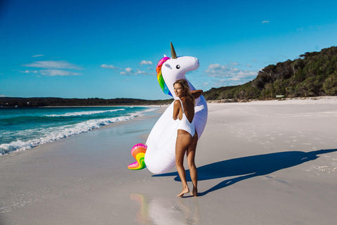 KOLOLO Giant Unicorn rainbow floaty girl at the beach walking with Unicorn looking back