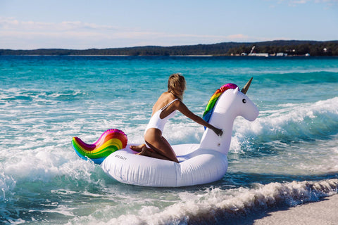 KOLOLO Giant Unicorn rainbow floaty girl at the beach sitting on floaty