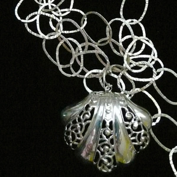 "This large openwork scalloped seashell makes a beautiful choker...or, wear it as a single charm on a linked bracelet... for an eye-catching piece of whimsy.  Sterling Silverr Clam on the Half Shell Charm. Handmade in America with love, and hand-sgned. Accompanied by a long leather cord or vintage inspired ribbon. 2-1/2"" x 2-1/4"" Also available as shoe clip."