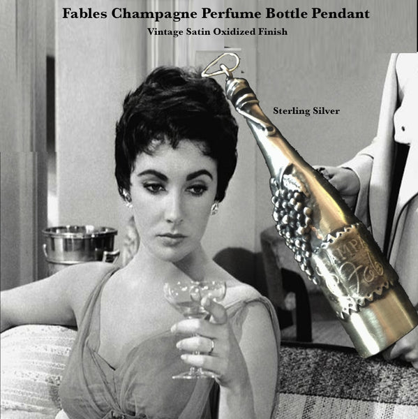 "Elizabeth Taylor with Fablesintheair Sterling Silver Champagne Perfume Bottle.When this cork pops...out wafts the smell of your favorite perfume, or aromatic oil... Fables Champagne... any imaginable scent..in an elegant sterling silver magnum. Fill with your favorite scent or oil. Puts you in the celebratory mood.  3-2/16"" x 1-1/2"" Approximately.  Sterling Silver Fables Champagne Perfume Bottle Charm. Comes on a sterling silver chain."