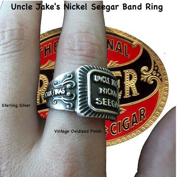 "Even if you are not a cigar aficionado, this vintage cigar band ring is ""smoking"". The first in what will be an expansive and whimsical collection,  this 3D version of an actual antique ""Seegar"" band--the first of its kind. Sterling Silver in my antique satin oxidized finish to bring the old cigar band to life once again!  Top 1/2"" wide approximately.  Made in the USA by hand. Hand signed.  Sterling Silver Uncle Jake's Nickel Seegar Cigar Band Ring.  Be sure to check out my other two cigar band rings--Mild"