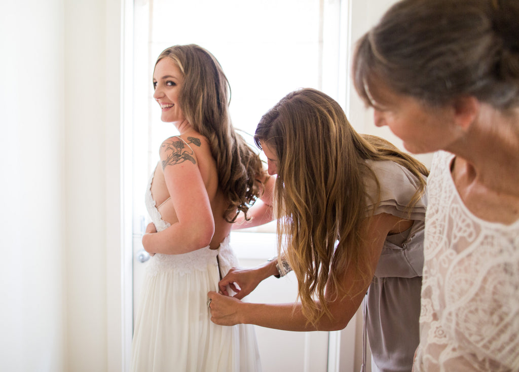 Her mom & sister help her button up into her dream gown.