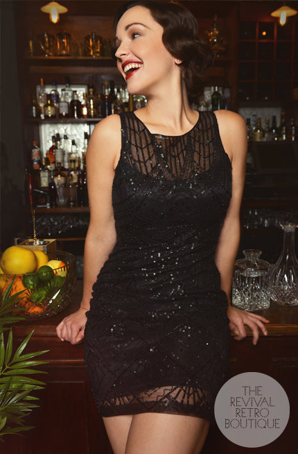 vintage girl wears 1920s party dress, she stands at the bar