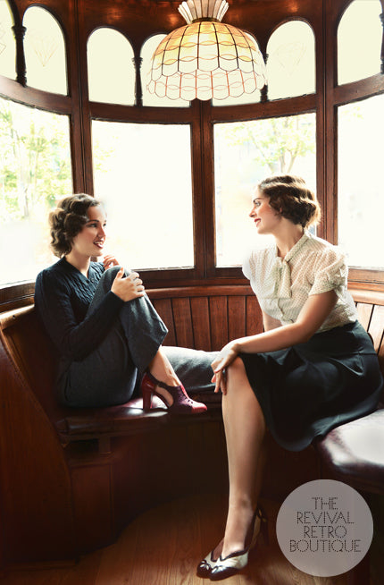 Two women sit in an old fashioned window seat, their clothing is 1940s inspired and both wear statement vintage shoes.