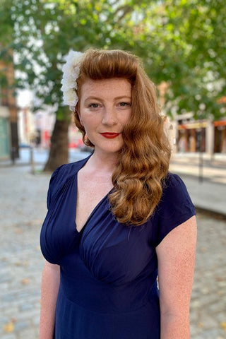 Red head woman in navy 1940s Piccadilly dress