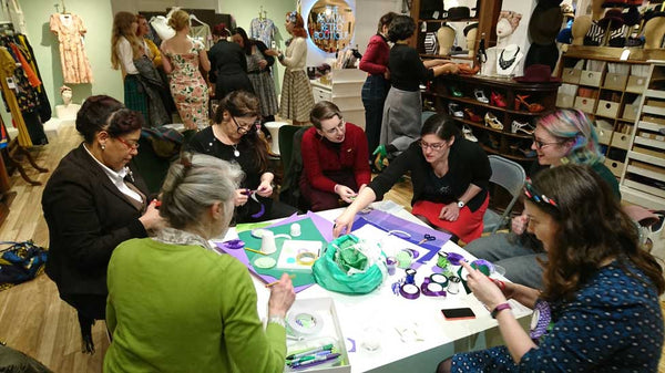 Women congregate crafting rosettes to wear for International Womens Day