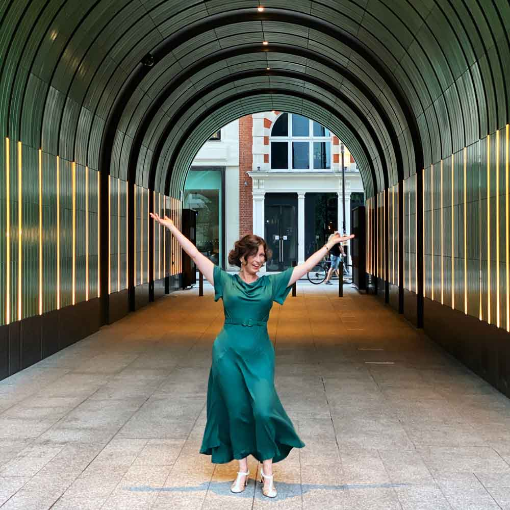 Woman wearing green dress jumps for joy