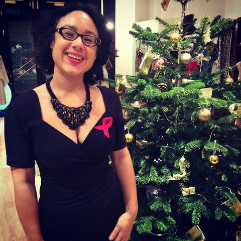 Owner Rowena smiling by the Christmas tree in store