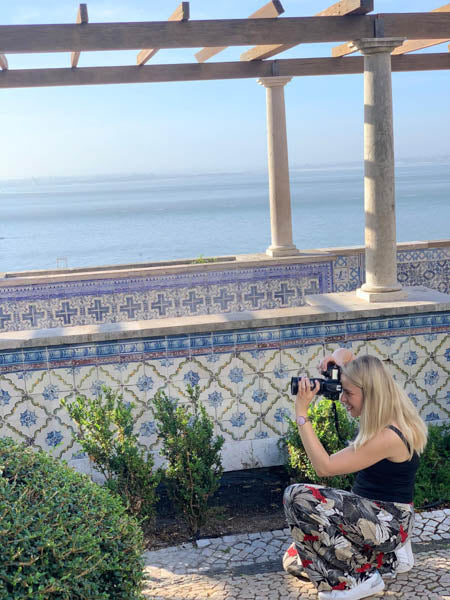 Photographer Tory Smith crouches to take picture against dramatic Lisbon ocesn view