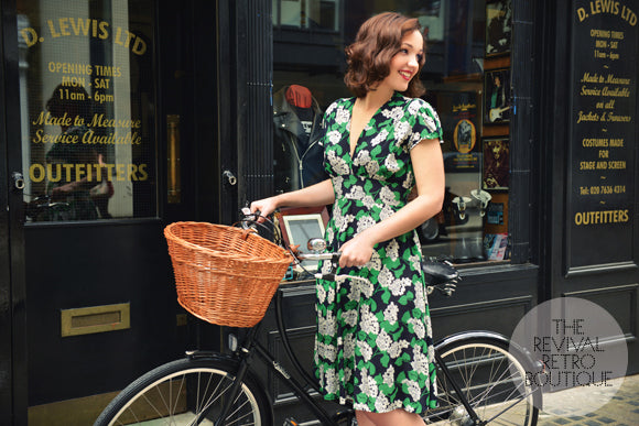 Woman stands with a bicycle wearing a Trashy Diva dress