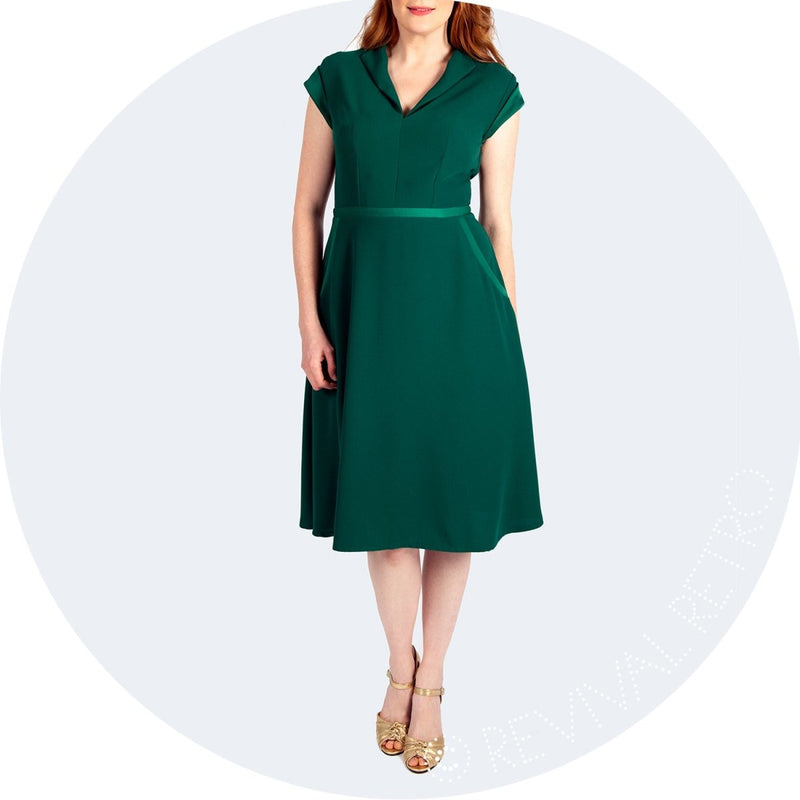 1950s Style Green Satin and Crepe Dress. A v-cut neckline, capped sleeve and an A line knee length skirt make this dress a winner for lots of different body shapes.  Nipping in at the waist it accentuates the narrowest point, giving a womanly, hourglass silhouette.  With the added contrast detailing on the  waistband, pockets and sleeves the Cambridge dress is a unique offering from our own range.