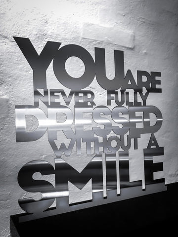 You are never fully dressed without a smile - Rustfri stål 33,5x32cm