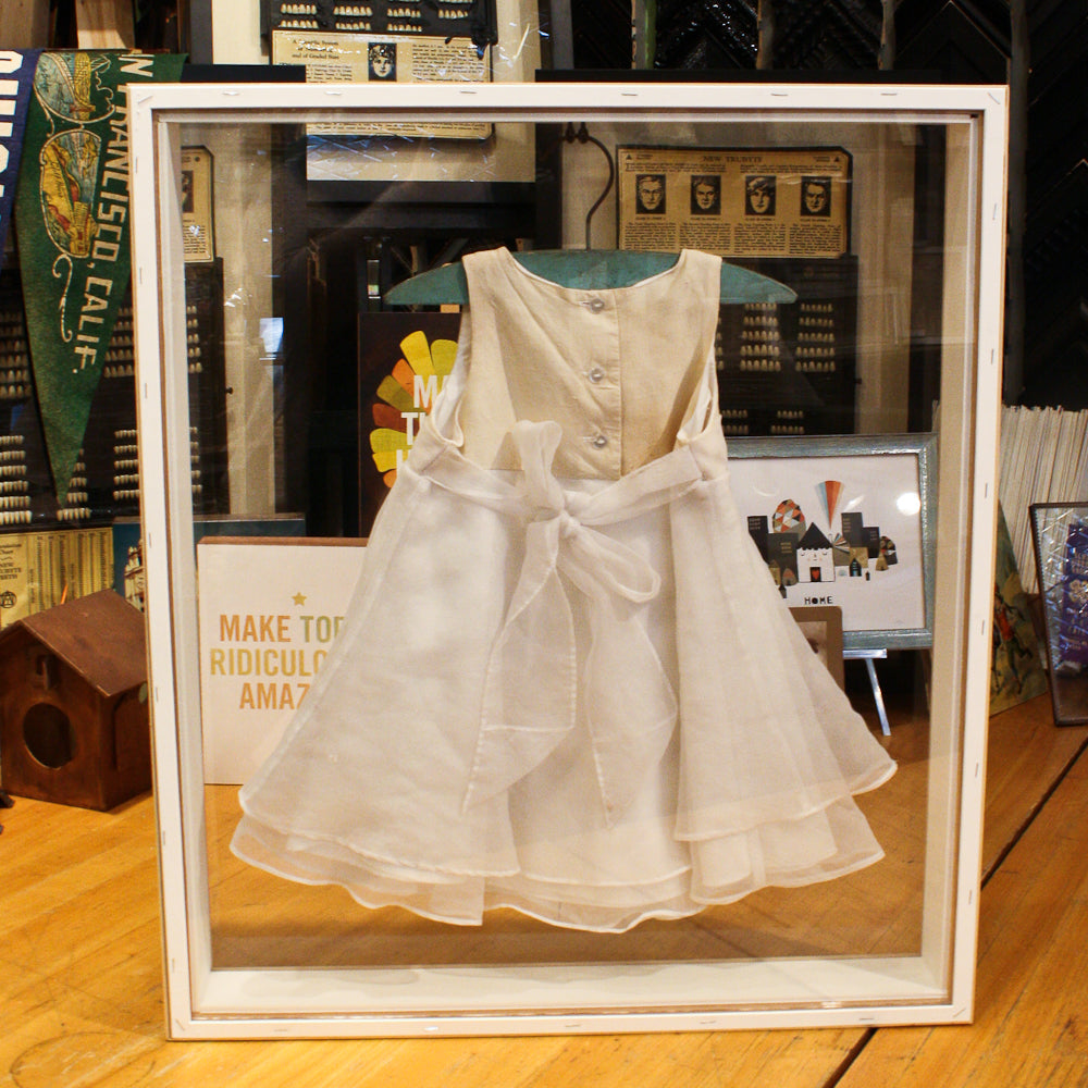 Christening gown framed in double glass custom shadowbox by Foursided Framing Boutique in Chicago