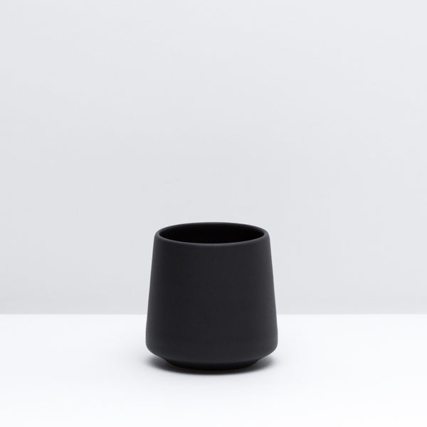 The porcelain wine cup in dusty black, our black glaze. Modern, handmade pottery, made in Detroit, Michigan.  USA Made.