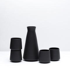 The Charlevoix Porcelain Wine Set including four wine cups and one decanter in Dusty Black, our black glaze. Modern, USA handmade pottery and unique gifts.Black Pottery.