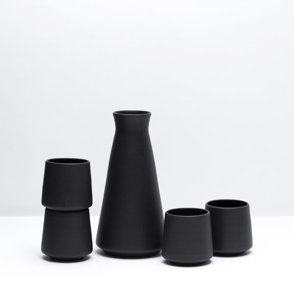 Porcelain Wine Set including four wine cups and one decanter in Dusty Black, our black glaze. Modern, handmade pottery. Black Pottery.