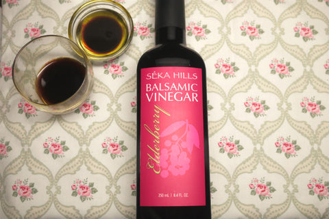 A 250ml bottle of Seka Hills Elderberry Balsamic Vinegar placed on the table along with a small jar of olive oil