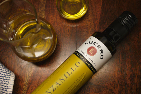 A 250ml bottle of Lucero Olive Oil placed on the wood table along with an olive oil jar.